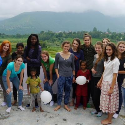 High school student volunteers doing building work in Nepal pose for a photo with young children and locals.